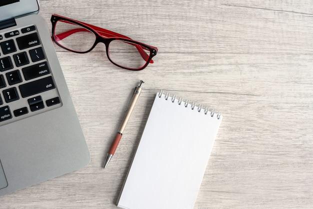 Zakelijk stilleven laptop glazen pen en notitieboekje op de licht houten tafel, bovenaanzicht