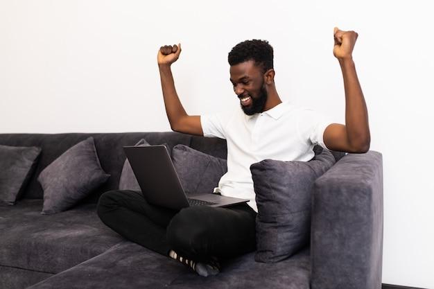 Zakelijk succes. opgewonden zwarte man met laptop gebaren ja vieren groot nieuws zittend op de bank binnen.