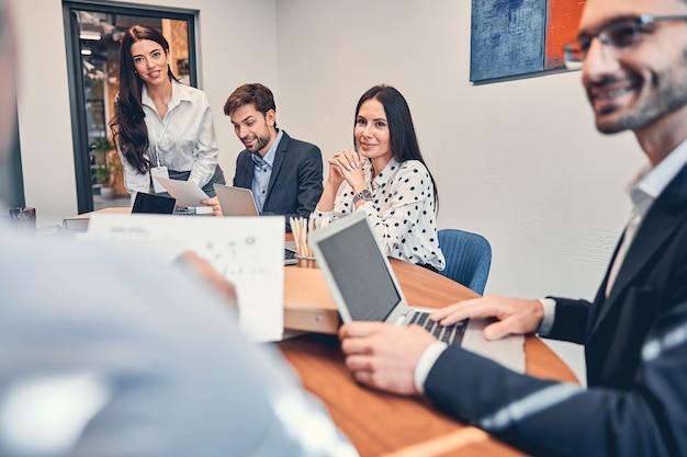 Zakelijk team gevormd uit jonge zakenlieden die aan het bureau zitten
