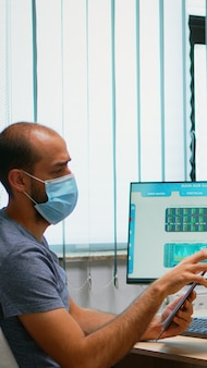 Zakelijk team met beschermingsmaskers met respect voor sociale afstand met behulp van plexiglas. freelancers die in een nieuwe normale kantoorwerkplek werken en schrijven op het klembord, zoeken op de computer.