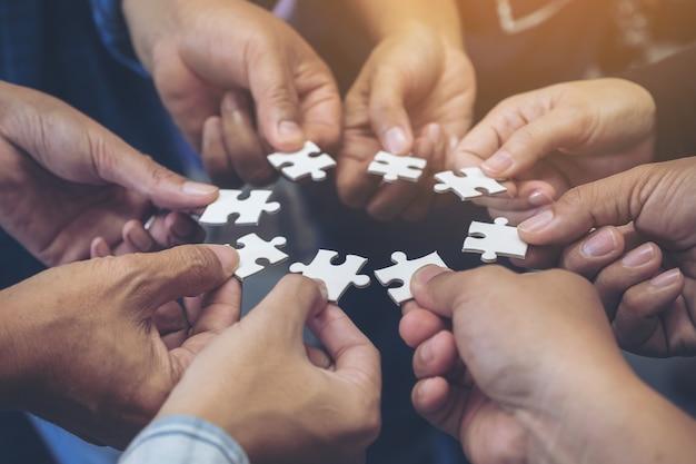 Zakelijk team staan en hun puzzel samen overhandigen