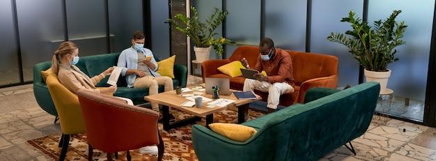 Zakelijk team tijdens de covid-uitbraak jonge multiraciale kantoormedewerkers die medische bescherming dragen