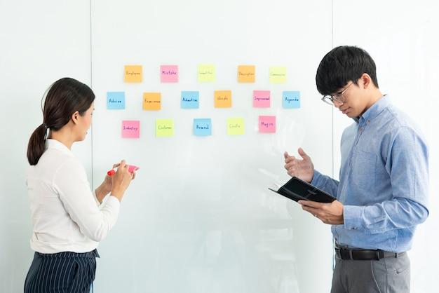 Zakelijk teamwerk in vergadering en zelfklevende notitie op spiegelbord bespreken met team in kantoorruimte voor het verzamelen van een idee brainstormplan.