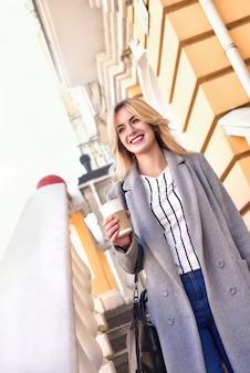 Zakelijk. vrouw met koffie lachend op straat