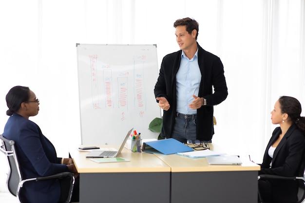 Zakelijk zakelijk leiderschapsconcept. spaanse creatieve man die spreekt in een ontmoeting met zwarte vriendinnen op het kantoor van de werkruimte.