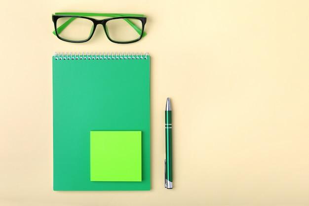 Zakelijke accessoires op desktop: notebook, agenda, vulpen, bril.