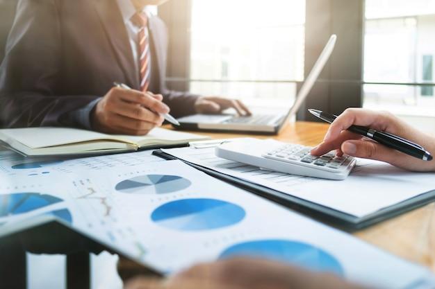 Zakelijke audits met behulp van een rekenmachine financieel gegevens beleggingsfonds op een werkplek, rijkdom concept