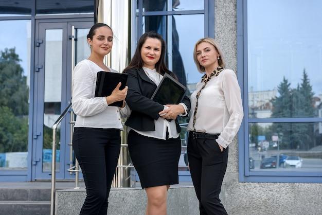 Zakelijke bijeenkomst buiten gebouw. drie jonge dames in pakken die informatie op tablet bespreken