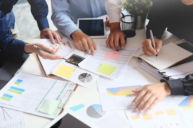 Zakelijke bijeenkomst met papieren grafiek en laptop computer tablet op tafel