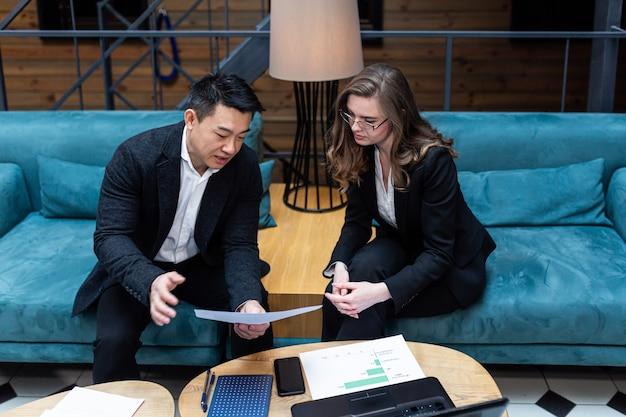 Zakelijke bijeenkomst twee zakenlieden aziatische man en vrouw zakelijke discussie internationale zakenpartners houden een vergadering