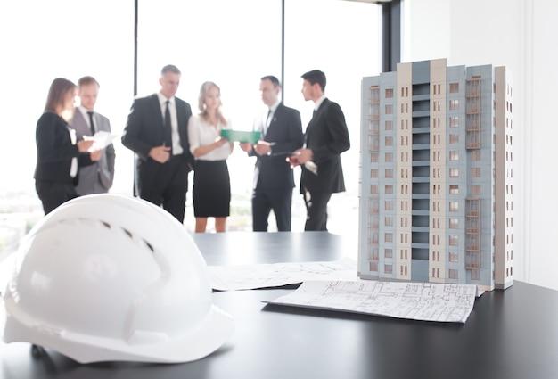 Zakelijke bijeenkomst van architecten en investeerders kijken naar model van moderne woonhuis met meerdere verdiepingen op tafel