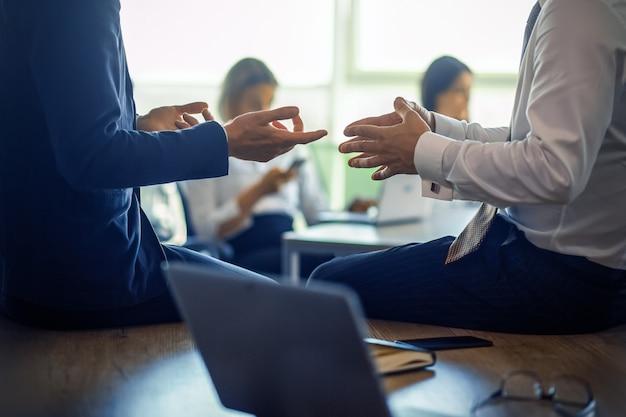 Zakelijke bijeenkomst van partners. close-up shot van menselijke handen gebaren tijdens discussie op voorgrond