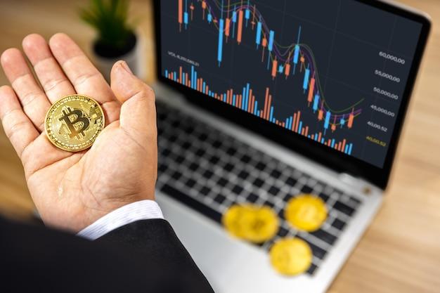 Zakelijke bitcoin bij de hand van investeerder met grafiek op laptop op houten tafel, beurs en forex finance concept