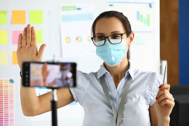 Zakelijke blogger in beschermend medisch masker begroet gesprekspartners via een smartphone.