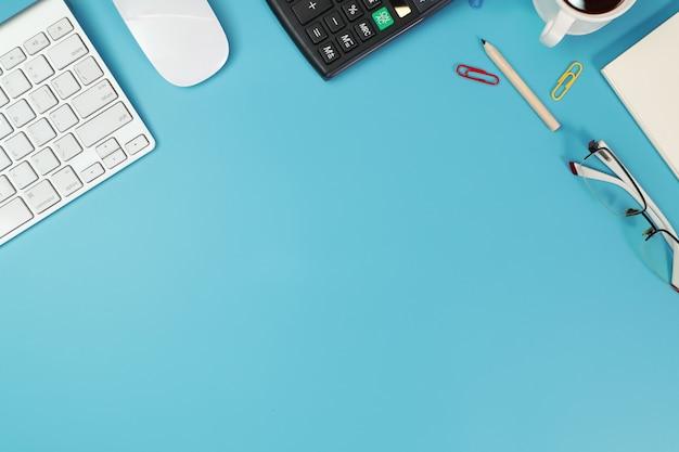 Zakelijke bureau met computer, bril, rekenmachine en potlood op blauw