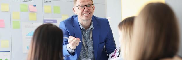 Zakelijke coach met een bril die informatie uitlegt aan luisteraars in het publiek
