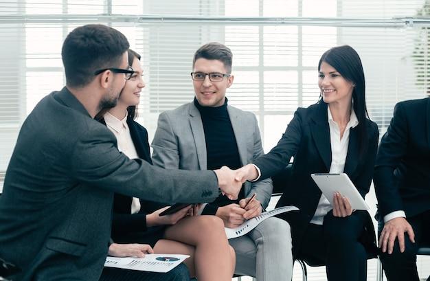Zakelijke collega's begroeten elkaar op een kantoorvergadering. concept van samenwerking