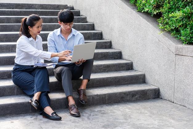Zakelijke collega's bespreken werkproblemen buiten in de buurt van het kantoorgebouw