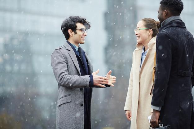 Zakelijke collega's chatten in besneeuwde straat