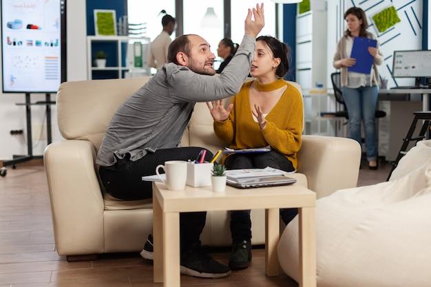 Zakelijke collega's die ruzie maken, elkaar schreeuwen tijdens werkuren zittend op de bank, terwijl diverse collega's bang op de achtergrond werken Premium Foto