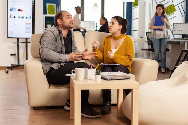 Zakelijke collega's die ruzie maken, elkaar schreeuwen tijdens werkuren zittend op de bank, terwijl diverse collega's bang op de achtergrond werken
