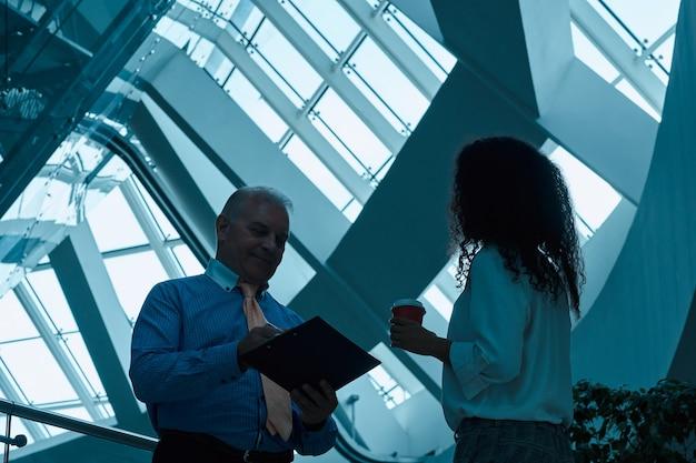 Zakelijke collega's die verduidelijkingen maken in het nieuwe contract