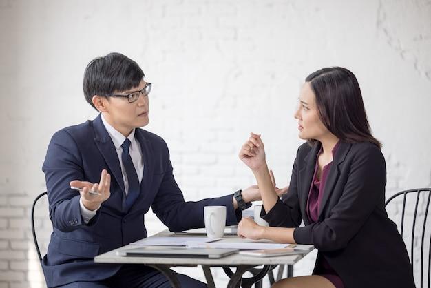 Zakelijke collega's praten samen op kantoor met een kopje koffie