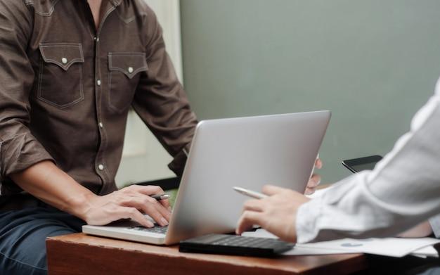 Zakelijke collega werken aan verslagdocumenten met laptop op een werkplek