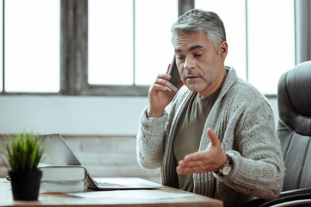 Zakelijke communicatie. aardige slimme zakenman die met zijn partner aan de telefoon praat terwijl hij hem het plan vertelt