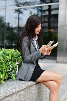 Zakelijke communicatieconcepten. jonge onderneemster gelukkig om mobiel te spelen.