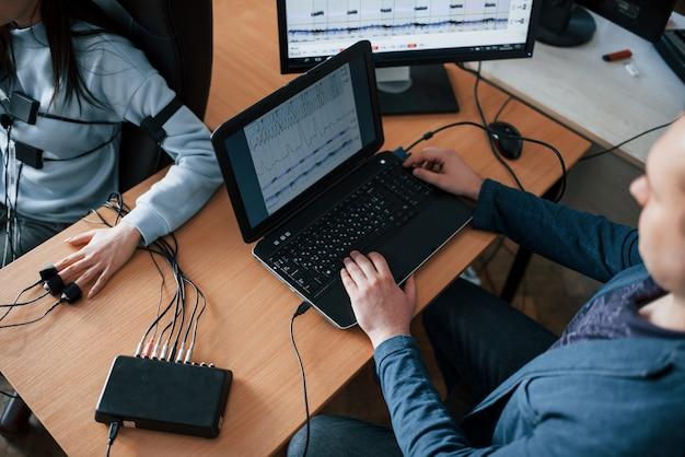 Zakelijke concurrent zit in de stoel. meisje passeert leugendetector in het kantoor. vragen stellen. polygraaftest