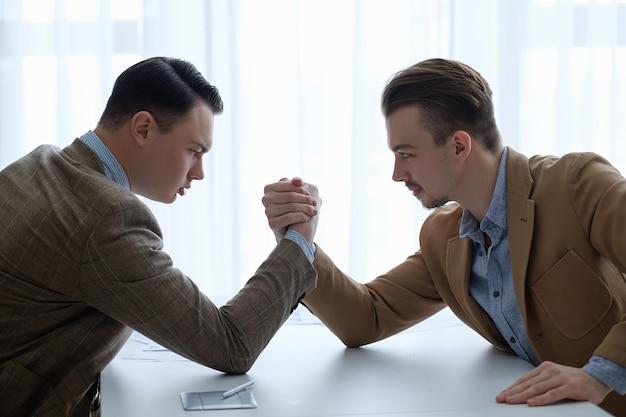 Zakelijke concurrentie en rivaliteit. arm worstelen strijd voor superiteit
