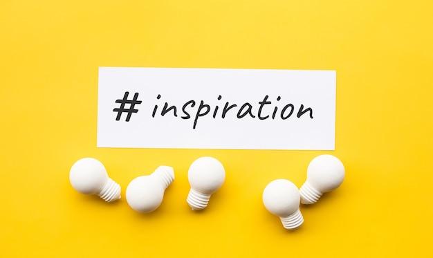 Zakelijke creativiteit met inspiratietekst en gloeilamp op gele achtergrond