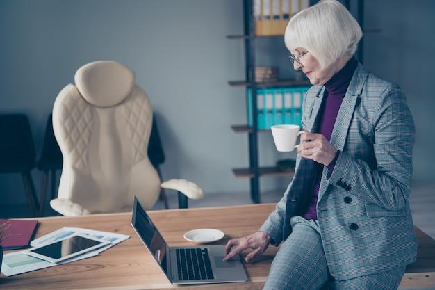 Zakelijke dame aan de balie die met laptop werkt