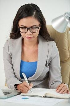 Zakelijke dame die aantekeningen maakt in planner