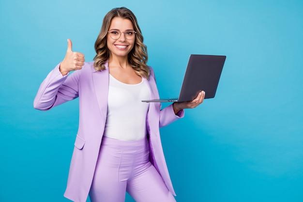 Zakelijke dame houden laptop duim opdagen als teken geïsoleerd op blauwe kleur