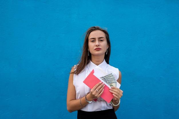 Zakelijke dame in handboeien met een envelop met dollars. concept van omkoping en corruptie