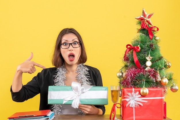 Zakelijke dame in pak met bril haar geschenk verrassend wijzend en zittend aan een tafel met een kerstboom erop in het kantoor