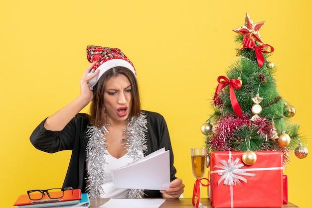 Zakelijke dame in pak met kerstman hoed en nieuwjaarsversieringen nerveus voelen en zittend aan een tafel met een kerstboom erop op kantoor