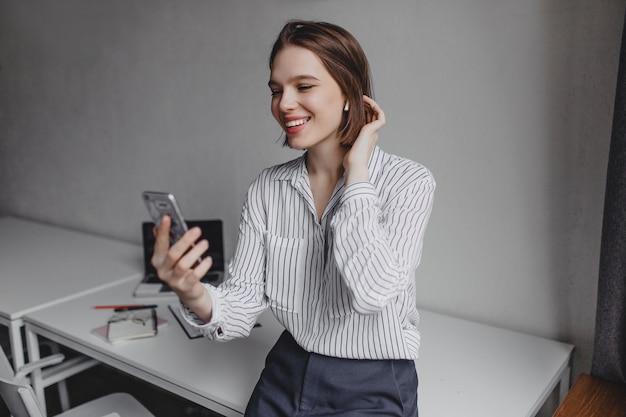 Zakelijke dame in wit overhemd is praten over telefoon video-oproep, glimlachend en leunend op witte tafel met laptop.