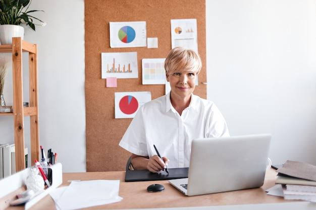 Zakelijke dame in wit overhemd zit in haar kantoor