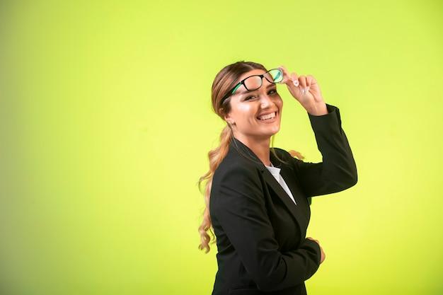 Zakelijke dame in zwarte blazer en bril ziet er positief uit