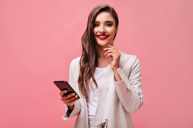 Zakelijke dame met rode lippen houdt telefoon op roze achtergrond. krullend brunette in kantoorkleding lacht en kijkt naar de camera.
