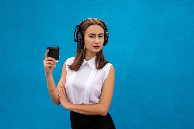Zakelijke dame pauzeert op het werk koffie drinken en luisteren naar muziek geïsoleerd op blauw