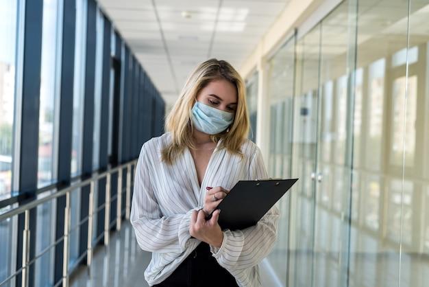 Zakelijke dame schrijft in een tablet terwijl ze in de gang van een modern zakencentrum staat