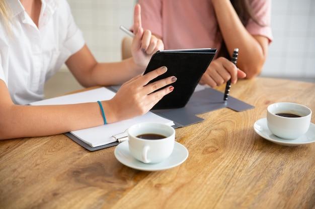 Zakelijke dames ontmoeten elkaar aan tafel, kijken naar presentatie op tablet, bespreken project of deal