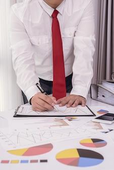 Zakelijke documenten op kantoor tafel met slimme telefoon en digitale tablet en man aan het werk
