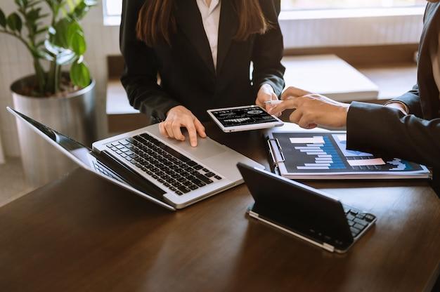 Zakelijke documenten op kantoortafel met slimme telefoon en rekenmachine digitale tablet en grafiekbedrijf met sociaal netwerkdiagram en twee collega's die gegevens bespreken die op kantoor werken