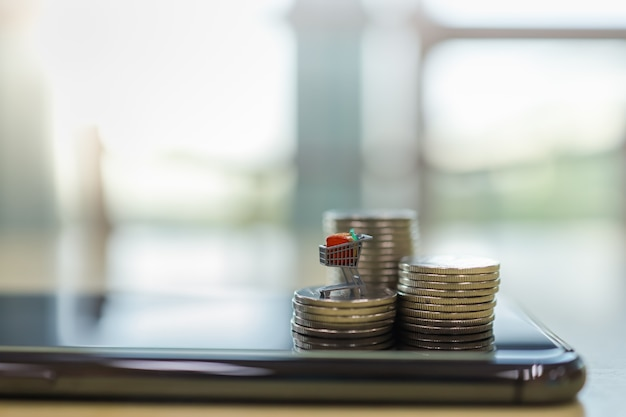 Zakelijke e-commerce en geld concept. sluit omhoog van boodschappenwagentje of karretje miniatuurcijfer bovenop stapel muntstukken bovenop op slimme mobiele telefoon