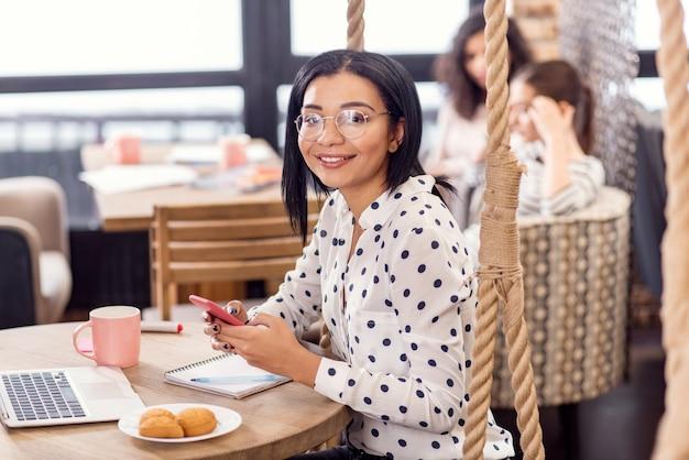 Zakelijke e-mail. homo vriendelijke charmante zakenvrouw camera staren terwijl het dragen van telefoon en grijnzend